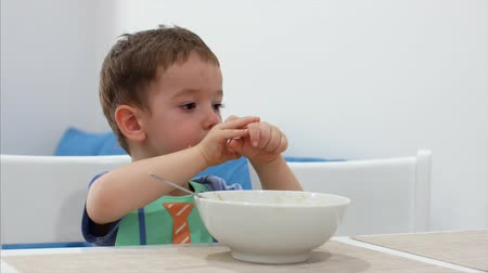 отпрыск : Small Cute Child is Sitting at a Table and eat his own oatmeal, the baby eats willingly. Concept Happy Childhood. Стоковые видеозаписи