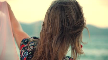 stal : Close up Portrait a Wonderful Brown-Haired Woman With Green Eyes with Flowing Hair in a Summer Dress with a Picture of Red and White Flowers Spinning Around with Scarf at a Beach at Set Sun.Soft focus Stockvideo
