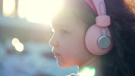 curly haired : Portrait of a Cute Child with curly hair, Caucasian Little Girl in a Pink Dress With a Pink Flower on Her Head in Her Hair,Baby in Pink Headphones Listening music,Looking at the Camera,Smiling Sweetly.