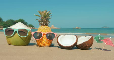 kokosový ořech : On a Tropical Beach Close-Up of Fruit in Sunglasses Under the Hot Summer Sun Along the Tropical Exotic Coast, Pineapple and Coconut in Sunglasses on the Ocean Background.Concept Summer, Party, Holiday Dostupné videozáznamy