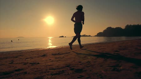 コミットメント : Young Man Athlete Running to the Length of the Beach at Sunset Background, Intense Cardio Exercise Training, Tropical Background, Slow Motion. Concept of Health, Sports, Cardio Exercise Training.
