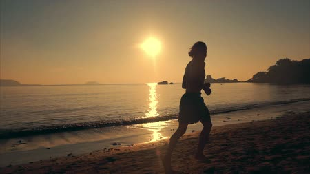 závazek : Young Man Athlete Running to the Length of the Beach at Sunset Background, Intense Cardio Exercise Training, Tropical Background, Slow Motion. Concept of Health, Sports, Cardio Exercise Training.