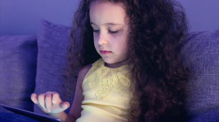 use laptop : Cute Child Entertaining With Tablet. Little Girl Spending Leisure Time Playing Mobile Game in the and Crushes the Bright Screen With Her Hand. Concept of:Happy Childfood, Technology, Childen Play Games.