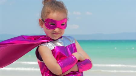герой : Beautiful Little Girl in the Superhero Costume, Dressed in a Red Cloak and the Mask of the Hero. Plays on the Background Sea and Blue Sky and Clouds, Sends a Fist Forward. Concept of a Happy Chilhood.
