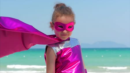 boyhood : Beautiful Little Girl in the Superhero Costume, Dressed in a Red Cloak and the Mask of the Hero. Plays on the Background Sea and Blue Sky and Clouds, Sends a Fist Forward. Concept of a Happy Chilhood.
