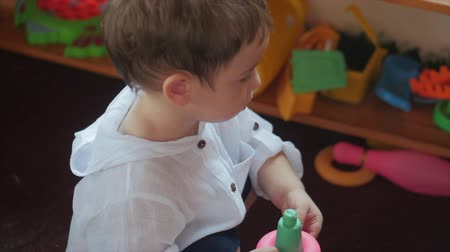 playful infant : Cute Little Child playing with Toys in Toy Room. Concept Happy Childhood. Stock Footage