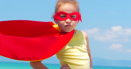 heroes : Close Up Portrait Beautiful Little Girl in the Superhero Costume, Dressed in a Red Cloak and the Mask of the Hero. Plays on the Background Sea and Blue Sky and Clouds. Concept of a Happy Childhood.