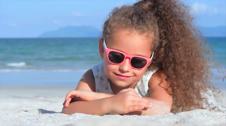 bronzlaşma : Close-Up Portrait of a Beautiful Little Girl in Pink Glasses, Cute Smiling Looking at the Camera, Lying on the Sand by the Sea, Pours Sand of Hand. Concept: Children, Childhood, Summer, Child, Kid. Stok Video