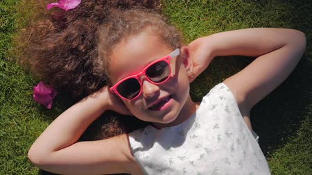 curly haired : Portrait of a Cute Child, a Wonderful Little Beautiful Girl in a White Dress and Pink Glasses, Lying on the Grass Looking at the Camera and Smiling Sweetly. Concept Of Happy Childhood. Stock Footage