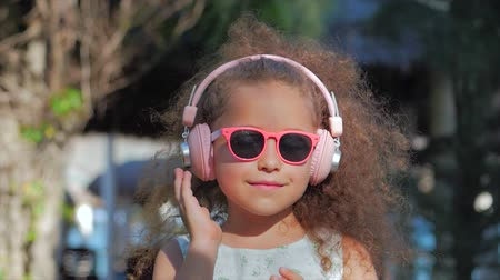 curly haired : Portrait of a Cute Child, a Wonderful Little Beautiful Girl in a White Dress With Pink Glasses and Pink Headphones, Looking at the Camera, Listening to Music. Concept Happy Childhood.