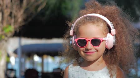 znuděný : Portrait of a Cute Child, a Wonderful Little Beautiful Girl in a White Dress With Pink Glasses and Pink Headphones, Looking at the Camera, Listening to Music. Concept Happy Childhood.