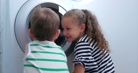 prát : Cute Children Looks Inside the Washing Machine. Cylinder Spinning Machine. Concept Laundry Washing Machine, Industry Laundry Service.