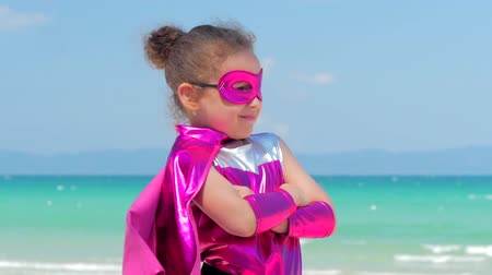 heroes : Beautiful Little Girl in the Superhero Costume, Dressed in a Red Cloak and the Mask of the Hero. Plays on the Background Sea and Blue Sky and Clouds, Sends a Fist Forward. Concept of a Happy Chilhood.