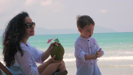 gently : Happy Mother Feeds Her Cute Child Coconut. Concept mom with baby outdoors, happy family, happy childhood, little baby. Concept Holiday, Vacation.