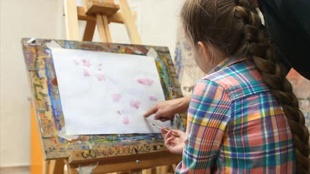 şövale : Little Girl artist draws at the easel. Drawing process: close-up of brush and canvas.
