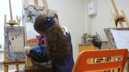 paleta : Young cute Female Artist is in an Art Studio, Sitting Behind an Easel and Painting on Canvas. Drawing Process: in the Art Studio of the Artists Hand Art Girl with a Brush Painting on Canvas. Dostupné videozáznamy
