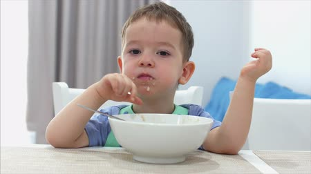 aveia : Small Cute Child is Sitting at a Table and eat his own oatmeal, the baby eats willingly. Concept Happy Childhood. Stock Footage