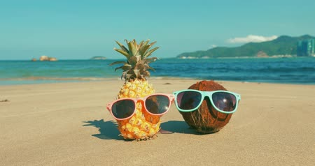 沿岸の : On a Tropical Beach Close-Up of Fruit in Sunglasses Under the Hot Summer Sun Along the Tropical Exotic Coast, Pineapple and Coconut in Sunglasses on the Ocean Background.Concept Topical Summer Holiday