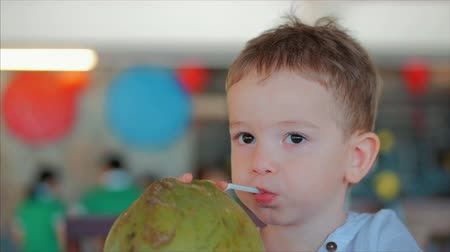 kokosový ořech : Cute Child Drinks a Coconut Trough a Straw, Close-Up. . Concept: Children, Happy Childhood, Summer, Baby, Vacation. Dostupné videozáznamy