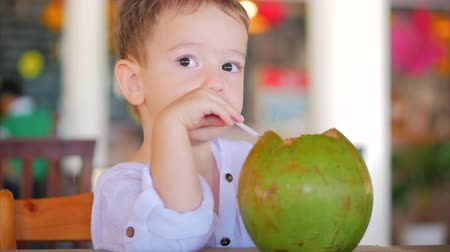 panelas : Cute Child Drinks a Coconut Trough a Straw, Close-Up. . Concept: Children, Happy Childhood, Summer, Baby, Vacation. Stock Footage