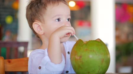 кухонная посуда : Cute Child Drinks a Coconut Trough a Straw, Close-Up. . Concept: Children, Happy Childhood, Summer, Baby, Vacation. Стоковые видеозаписи