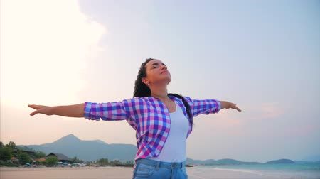 braços levantados : Woman with arms raised On a Tropical Beach Close-Up Portrait of European Beautiful Cute Brunette, Young Woman or Cheerful Girl lifting Arms Up Celebrating Life Scenic Landscape, Blowing Wind Hair the Wind , Slow Motion.