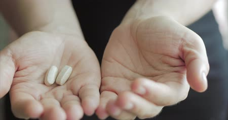 aszpirin : Close-up of Female Hands, Someone Pours a Bunch of Prescription Opiate Pills into the Hand. Concept of Health, Drugs, Contraception.