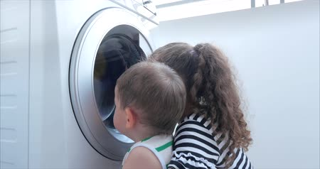 rakomány : Cute Children Looks Inside the Washing Machine. Cylinder Spinning Machine. Concept Laundry Washing Machine, Industry Laundry Service.