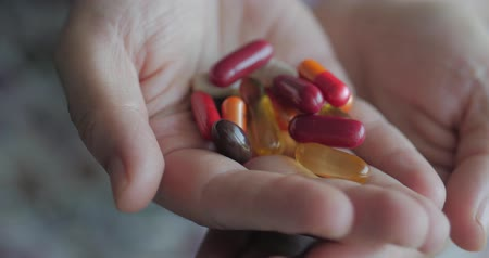 dispensing : Close-up of Female Hands, Someone Pours a Bunch of Prescription Opiate Pills into the Hand. Concept of Health, Drugs, Contraception.