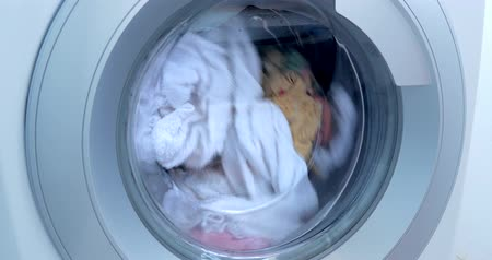 prát : Loading the washing machine. Industrial Washing Machine Washes Colored Clothing and White Linen, White Striped Clothing. Cylinder Spinning Machine. Concept Washing Machine, Industry Laundry Service.