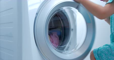 podložka : Load clothes to the washing machine. Little Girl Loads the Laundry in the Washing Machine and includes washing. Concept Laundry Washing Machine, Industry Laundry Service.