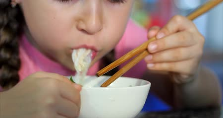 отпрыск : Cute Small Child is Sitting at a Table and Eat His Noodles, the Baby Eats Willingly. Little Girl Eating Noodles With Chopsticks. Concept Happy Childhool.