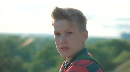 magasság : Close up Portrait Caucasian Boy Teenager in a red shirt with a backpack on his back, at sunset, sitting on a high hill enjoying warm summer vacation. Stock mozgókép