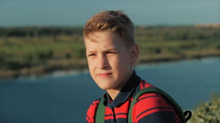 looking distance : Close up Portrait Caucasian Boy Teenager in a red shirt with a backpack on his back, at sunset, sitting on a high hill enjoying warm summer vacation. Stock Footage