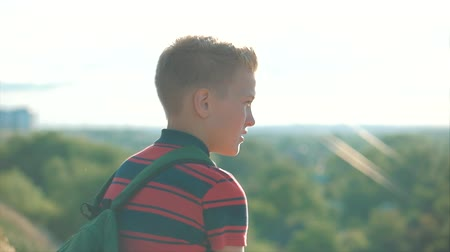 magasság : Teenager in a red shirt with a backpack on his back, at sunset, sitting on a high hill and looking at the clouds in the sky, nature, river, trees.