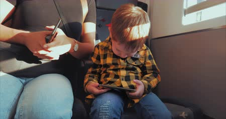 use laptop : Cute Child Entertaining With Tablet. Little Boy Spending Leisure Time, Rides an Electric Train with His Mother, Playing Mobile Game in the and Crushes the Bright Screen With Her Hand. Happy Family.