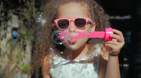 outside : Happy Little Girl playing outdoor, blowing soap bubbles, having fun on backyard. Nature. Beautiful Child in Park.
