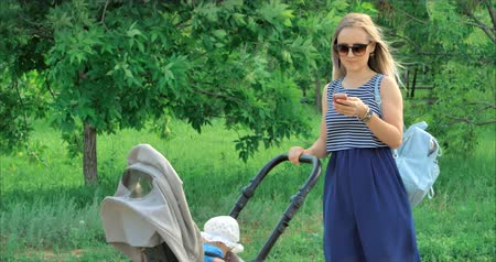 iyi bir ruh hali : Happy young mom with glasses typing text messages on the phone device, walking with a small child on the street. Stok Video