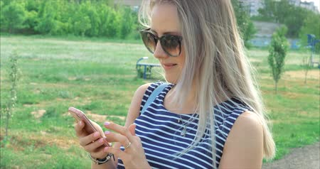 хорошее настроение : Happy young woman with glasses typing text messages on the phone device.