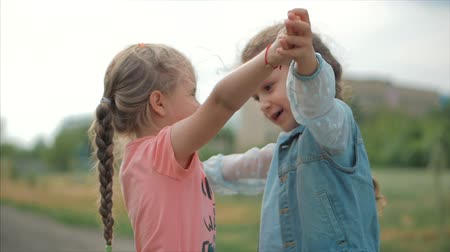 két : Two smiling, curly, cute sisters baby-girls hug tightly each other. Happy childhood, positive emotions, true feelings.