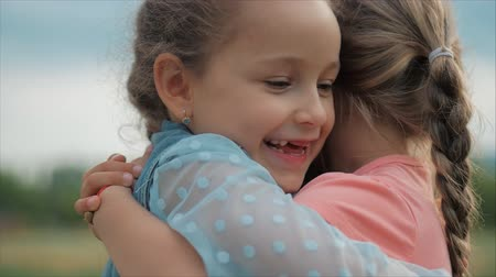 verdadeiro : Two smiling, curly, cute sisters baby-girls hug tightly each other. Happy childhood, positive emotions, true feelings.