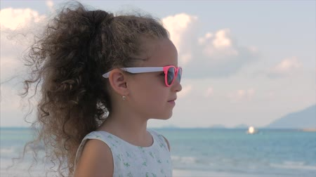 famiglia spiaggia : Close-up Portrait of a Beautiful Little Girl in Pink Glasses, Cute Smiling, Looking at the Sea. Concept: Children, Childhood, Summer. Filmati Stock