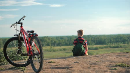 magasság : Teenager in a Red T-Shirt With a Backpack on his Back, at Sunset, Sitting on a High hill, Enjoying Nature, Freedom, Against the Background of his Bike.