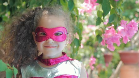 boyhood : Beautiful Llittle Girl in the Superhero Costume, Dressed in a Pink Cloak and the Mask of the Hero. Plays on the Background of the Sea and the Blue Sky and Clouds, Corrects the Pink Mask on His Face