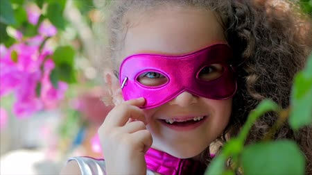 plášť : Beautiful Llittle Girl in the Superhero Costume, Dressed in a Pink Cloak and the Mask of the Hero. Plays on the Background of the Sea and the Blue Sky and Clouds, Corrects the Pink Mask on His Face