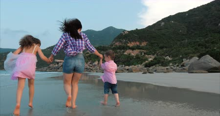 anne : Young Family, Mother and Children are Walking Along the Coast. Happy family walking on sea coast.
