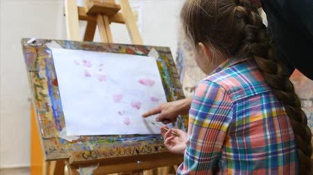 cavalete : Little Girl artist draws at the easel. Drawing process: close-up of brush and canvas.