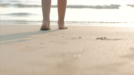 suntan : Silhouette of childrens Feet walking on wet sand in along a tropical beach on a tropical ocean background. Concept: Children, Happy Childhood, Summer, Child, Vacation. Soft focus. Stock Footage