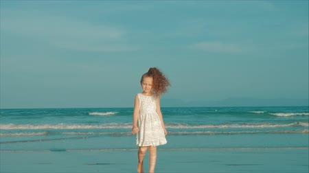 vacation : Curly little girl in white dress walking on the beach at sunset. Slow Motion. Happy Childhood, Freedom and Travel concept.