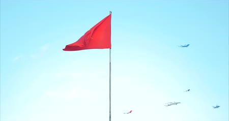 north vietnam : National Flag of Vietnam hovers against the blue sky and flying kites. 4K video of Vietnam flag with flag . The national flag is red with a big gold star.